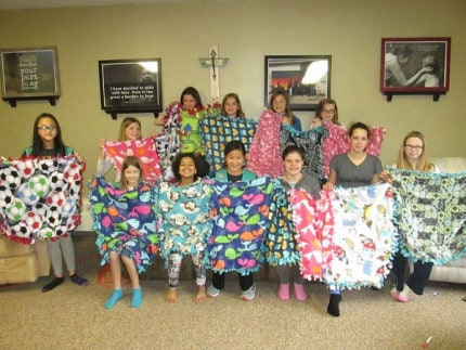 Photo provided by Kelly Stoker. Members of Troop 40076 display some of the blankets they made for orphans in China.