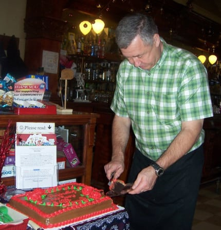 Photo by Lisa Carolin. Randy Seitz cuts a special 100th anniversary chocolate cake last Saturday during Chelsea's chocolate Extravaganza.
